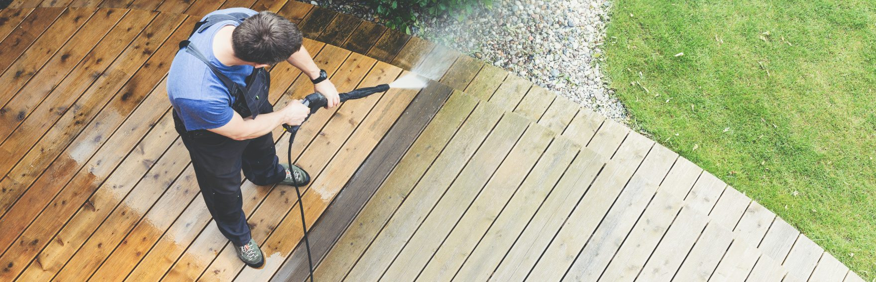 Media Blasting vs Sandblasting Phoenix man cleaning terrace with a power washer - high water pressure cleaner on wooden terrace surface